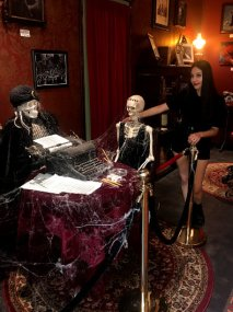 Mysterious skeletons sit around a table with a typewriter
