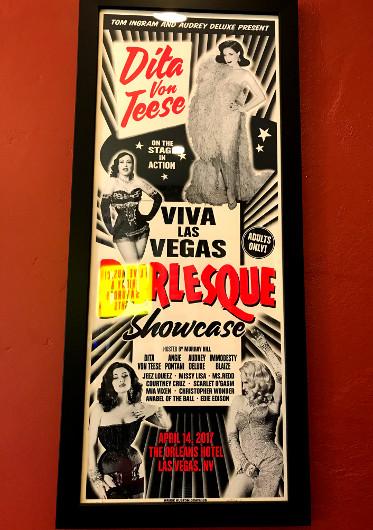 A framed poster advertising a burlesque show featuring Dita Von Teese
