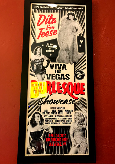 A framed poster advertising a burlesque show featuring Dita Von Teese